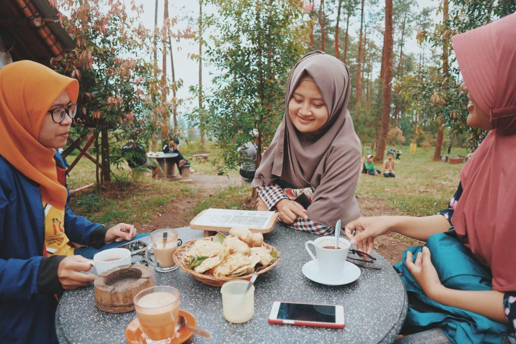 Three people having food outside